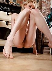 Beautiful blonde Cate is feeling randy and decides to get naked in her kitchen. She has dropped her dress and panties, so take a closer look at her tight ginger pussy hair.