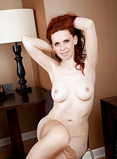 Redhead milf strips off her dotted panties to spread her hairy snatch