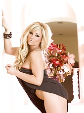 Hot busty blonde pornstar, Tyler Faith, poses in her sexy black dress and then lifts it so you can see she has no panties on!