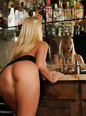 Sexy busty blonde, Mary Carey, poses with two of her favorite things.  A stocked bar and some sexy black lingerie get Mary so turned on and horny!