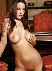 A shiny black cut-out body suit exposes all the right parts of busty brunette, Nikki Nova