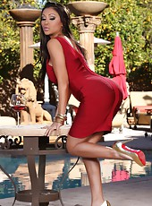 Beautiful busty Indian, Priya Rai, poses outdoors in her tight red dress.  She