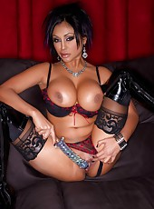 Busty Indian babe, Priya Anjali Rai, poses in her thigh high boots, stockings and sexy lingerie.  She gets so turned on she just has to pleasure her pussy with her glass toy!