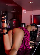 Hot and sexy Priya Anjali Rai climbs up on the counter and shows off her big boobs and clean shaven pussy.