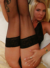 Blonde milf in black lingerie fingers her pussy for the camera