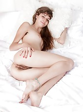 Willow is a petite and sexy American all-natural beauty, and lays in her attractive black dress and stockings. She rubs her hairy pussy through her red thong, but then gets naked while stroking her pussy.