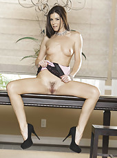 Foxy brunette with beautiful trimmed pussy and long legs strips in high heels