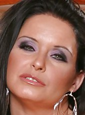 Dark haired office lady Maya Devine is showing her milf titties on camera