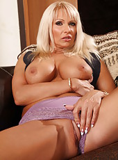 Pretty and tanned milf Winnie plays with her shaved pussy and gets pleasure