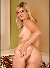 Naughty cougar bitch Alana Thomas doing a striptease and playing with pussy