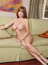 Dazzling coquette Darla Crane playing with her boobies on the sofa
