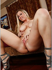 Milf beauty Devon Lee is spreading her legs on a brown sofa