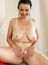 Elegant and busty brunette Leona Sweet lets loose her massive mams