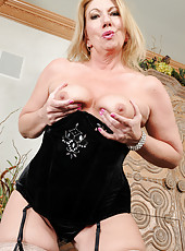 Sexy 53 year old Summer Sands slips off her slinky black lingerie