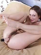 Izolda strips from her grey dress to lay naked on the bed. She spreads her legs and opens up her hairy pussy. Then, she pulls out her favorite vibrator and masturbates while getting her pussy all wet.