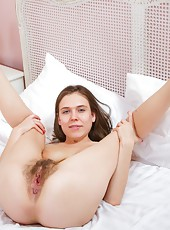 Agneta dresses sexy in purple on her bed and we peek up her skirt at her hairy pussy by picture 16. From there, she strips from her lingerie to show off her beautiful all-natural body and her hairy pussy.