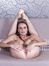 Izolda has sexy legs and a beautiful all-natural body. She shows off her legs and ass while looking hot in white lingerie. A hot striptease leads to her spreading her legs and tugging at her hairy pussy.
