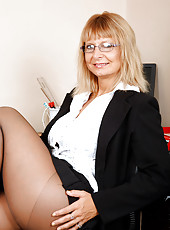 Office milf Alex shows off her big cleavage and giving a seductive look indoors