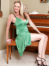 Charming milf shows her mouth watering cleavage in a tight green evening dress