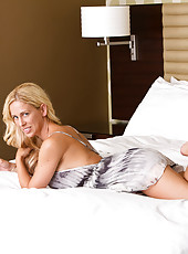 Gorgeous blonde milf teases on her bed in a skimpy dress