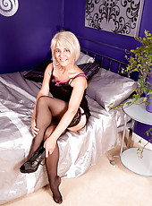 Glamorous blonde milf Dana teases us in her sexy black lingerie in the bedroom