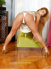 Long haired tanned blonde Anilos bends over revealing a tasty view of her ample rump