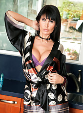 Voluptuous housewife Eva Karera entices as she lets her robe drop in the kitchen