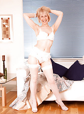 Lovely cougar milf unbuttons her cute dress ready to reveal her sexy white undies on the sofa