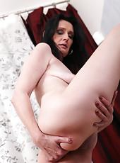Mature mom Laura Dark digs her fingers deep into her juicy twat