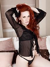 Redhead beauty Mystique struts her stuff in black lingerie