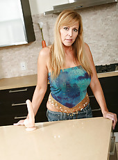 Nicole Moore shows off her decadent milf curves in a short jean mini skirt
