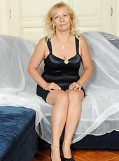 Milf babe Sara Lynn slides off her black bra to flaunt her curvy cougar body