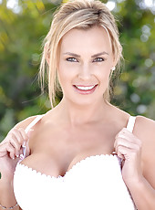 Blonde mature Tanya Tate shows off her tempting cleavage as she slowly strips beside the pool