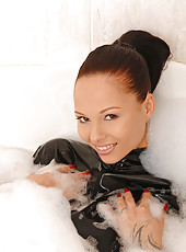 Busty Dominno having bath in latex