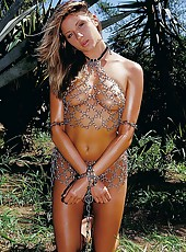 Bronzed beauty Monica chained up